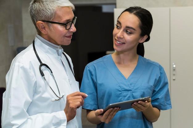 Médico sorridente e enfermeira conversando