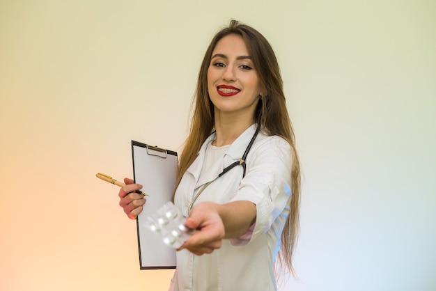 Médico sorridente oferecendo comprimidos na bolha. mulher usando uniforme médico e luvas de proteção