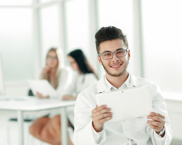 Médico sorridente olhando para a tela do tablet digital