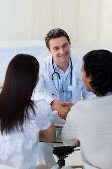 Médico sorridente que explica o diagnóstico para um casal