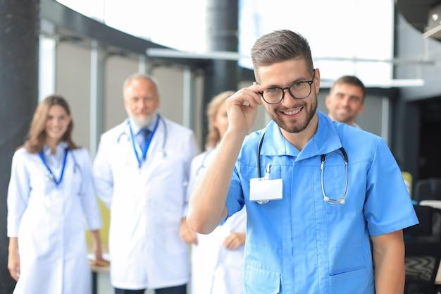 Médico sorridente segurando o tablet na frente de sua equipe médica.