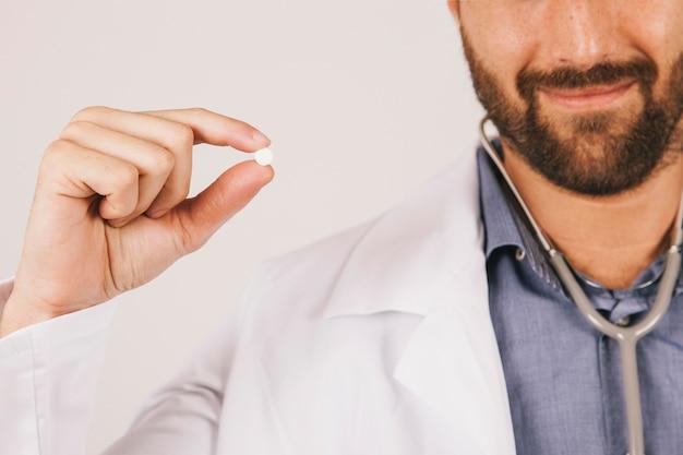Médico sorrindo e segurando uma pílula Foto gratuita