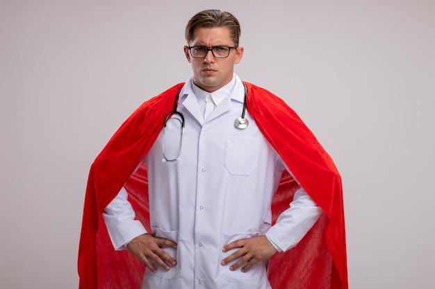 Médico super-herói homem vestindo jaleco branco com capa vermelha e óculos com estetoscópio ao redor do pescoço, olhando para a câmera com expressão séria e confiante com os braços na altura do quadril sobre fundo branco