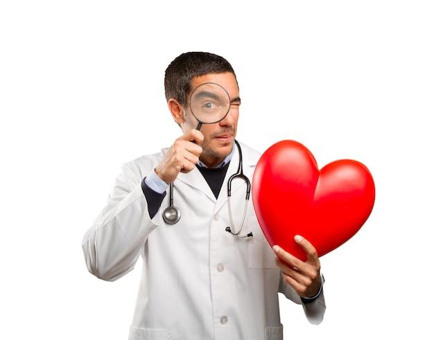 Médico surpreso usando uma lupa contra um fundo branco