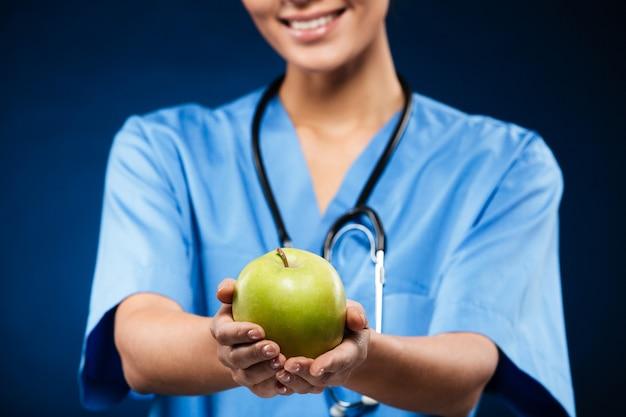 Médico swith estetoscópio segurando e mostrando a maçã verde
