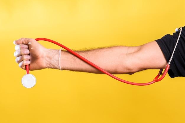 Médico tem na mão um estetoscópio, isolado no fundo amarelo do estúdio.