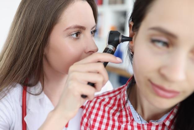 Médico terapeuta examinando a orelha de uma paciente com ostoscópio na clínica
