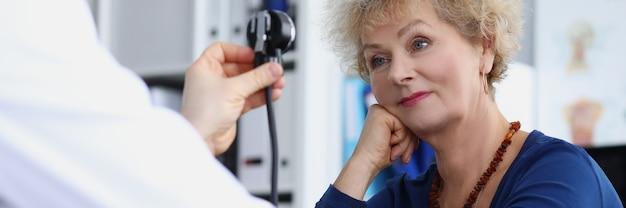 Médico terapeuta mede a pressão arterial de mulheres idosas