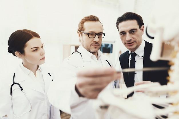 Médico terapeuta mostra vértebras cervicais problema