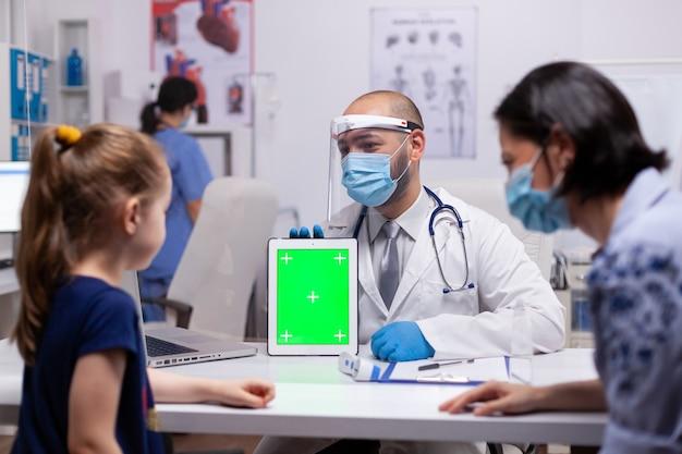 Médico terapeuta usando tablet de tela verde para exame no consultório médico. pediatra com luvas de proteção e máscara contra covid19 falando sobre tratamento de doenças proporcionando cuidados de saúde