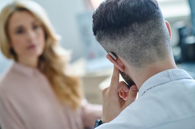 Médico testando aparelho auditivo e paciente do sexo feminino