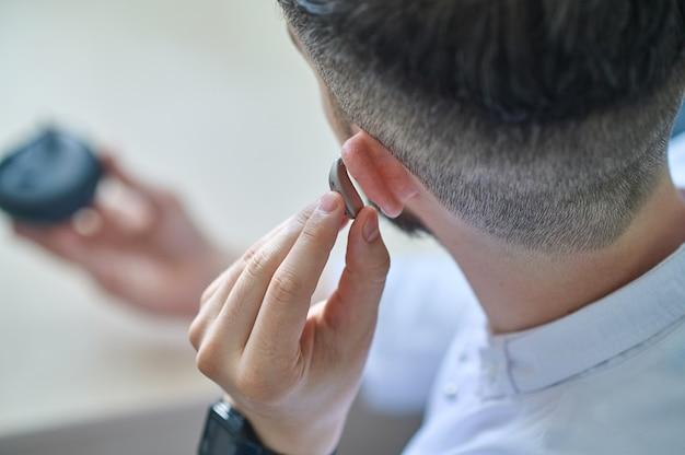 Médico testando aparelho auditivo em seu ouvido
