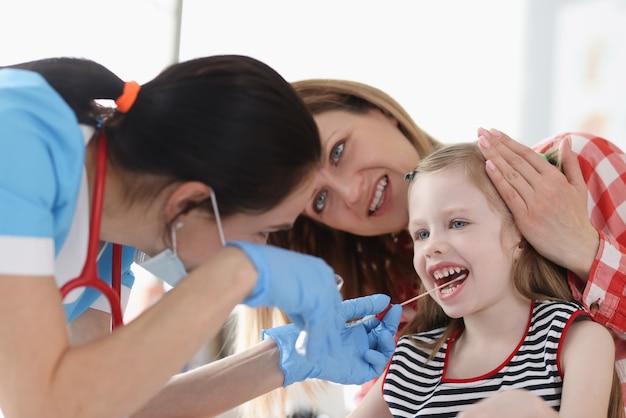 Médico tirando amostra de dna bucal de uma garotinha na clínica