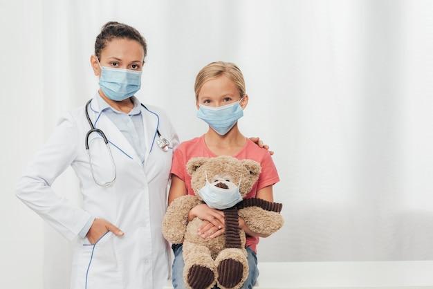 Médico tiro médio e criança com urso
