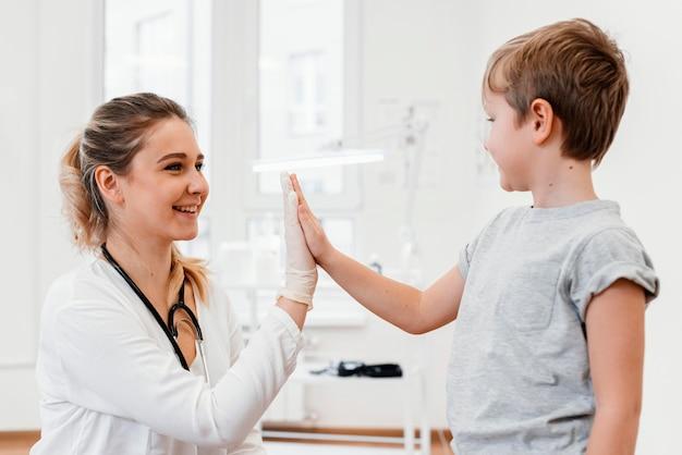 Médico tiro médio e criança levantando a mão
