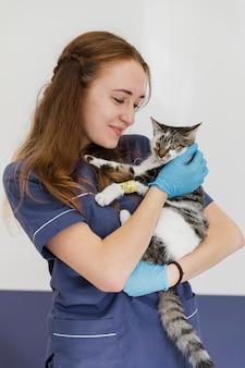 Médico tiro médio, segurando o gato com lesão na perna