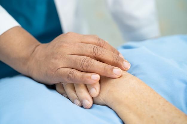 Médico tocando a mão paciente sênior asiática com amor.