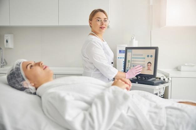 Médico tocando a tela de uma máquina de dermoabrasão com a mão enluvada antes de um procedimento de beleza