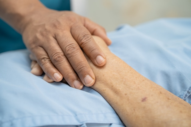 Médico tocando as mãos paciente sênior asiática com amor.