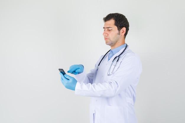 Médico tocando smartphone com dedo no jaleco branco, luvas e olhando sério.
