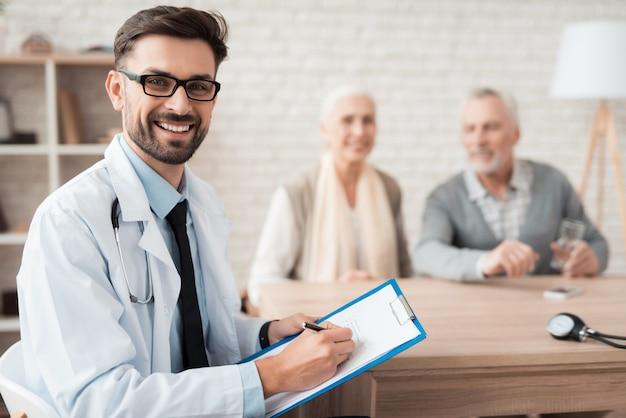 Médico toma notas ao examinar o casal de idosos.