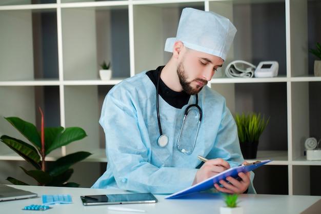 Médico trabalha em uma mesa no consultório da clínica.