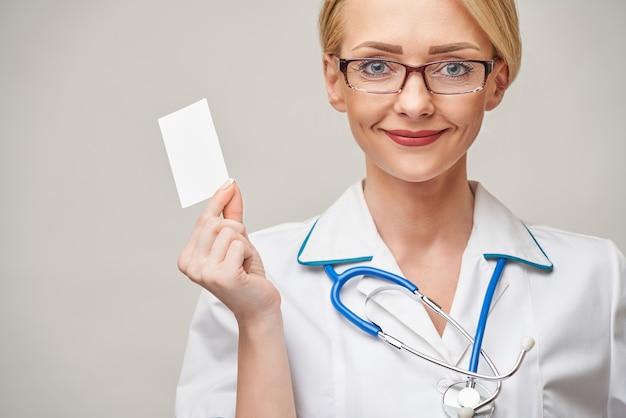 Médico trabalhador ou enfermeira mostrando um cartão de visita em branco