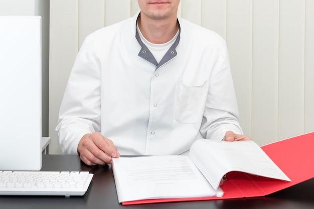 Médico trabalhando com computador e escrevendo na papelada
