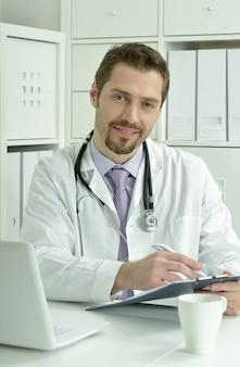 Médico trabalhando com laptop no escritório