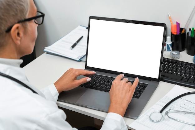 Médico trabalhando em um laptop vazio
