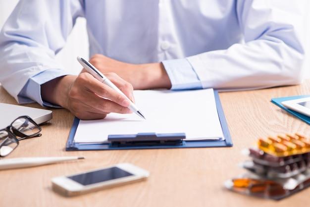Médico trabalhando em uma mesa de madeira na clínica
