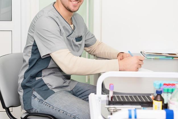 Médico trabalhando, escrevendo na papelada