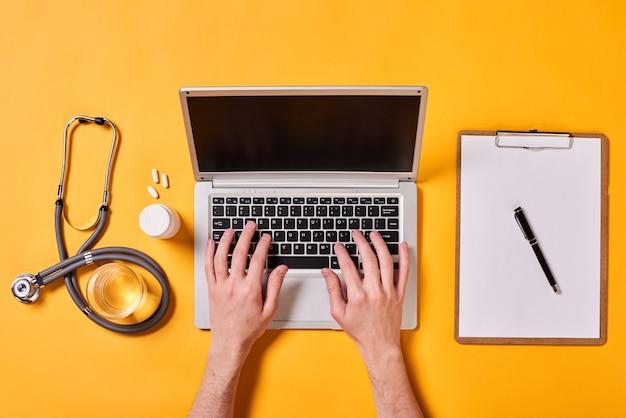 Médico trabalhando no laptop plano