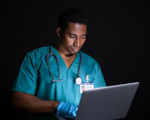 Médico trabalhando no laptop, tiro médio