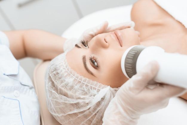 Médico trata o rosto de mulher em salão de beleza.
