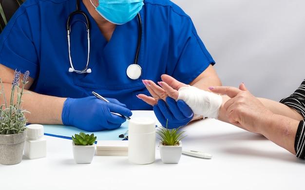 Médico traumatologista em luvas médicas de látex azul senta-se em uma mesa e mantém uma recepção do paciente com uma lesão na mão