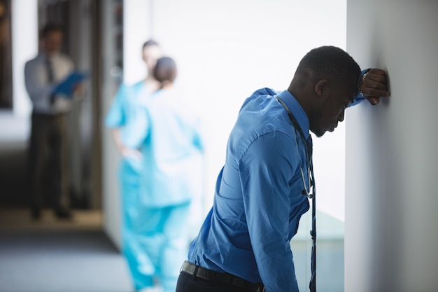 Médico triste encostado na parede