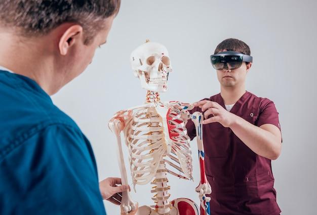 Médico usa óculos de realidade aumentada e esqueleto humano para ensinar aluno