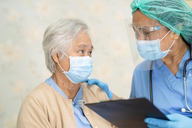 Médico usando estetoscópio para verificar paciente asiática idosa ou idosa usando máscara facial no hospital para proteção contra infecção por covid-19 coronavirus.