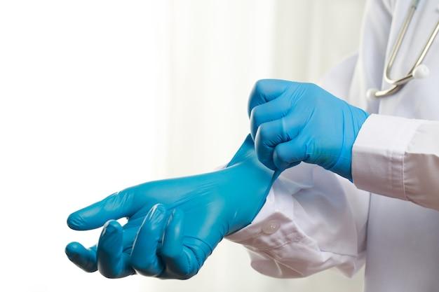 Médico usando luvas de borracha azuis para proteção contra covid-19 no hospital Foto Premium