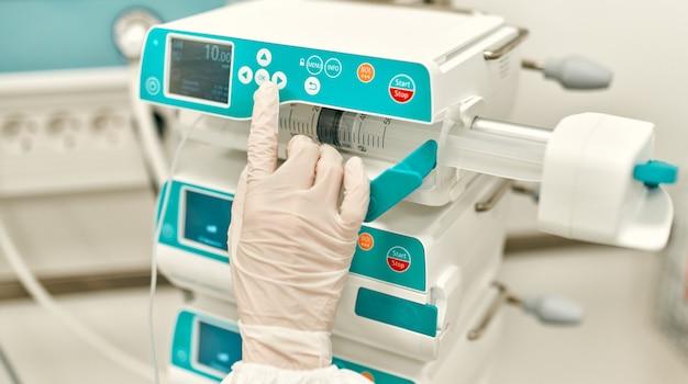 Médico usando luvas de proteção pressiona um botão em uma máquina de medicamentos