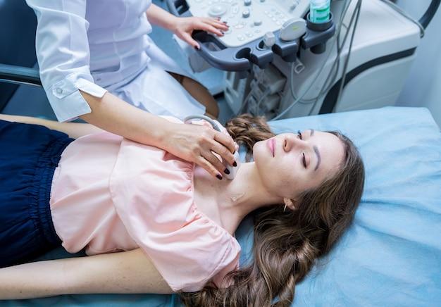 Médico usando máquina de ultra-som para examinar a tireóide de uma mulher