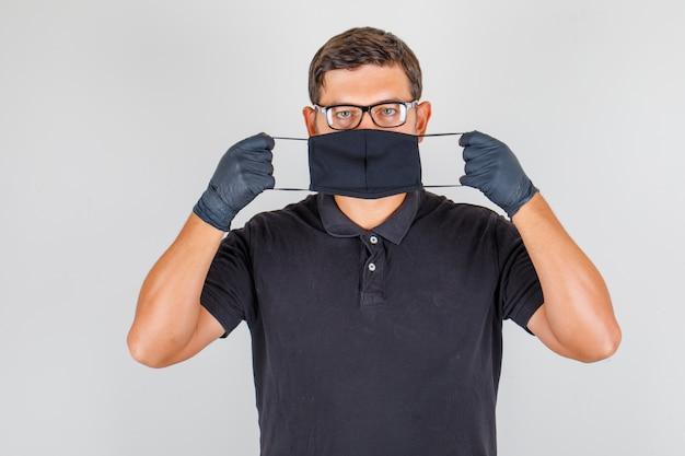 Médico usando máscara de camisa polo preta e olhando sério