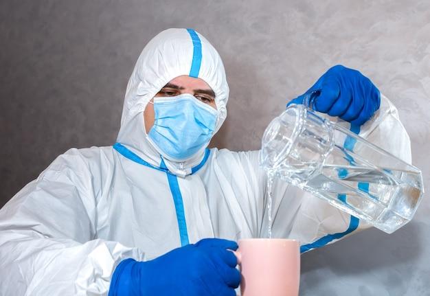 Médico usando roupa de proteção médica, máscara e luvas, despejando água para o teste. protetores contra epidemia de vírus. coronavírus (covid-19). conceito de saúde.