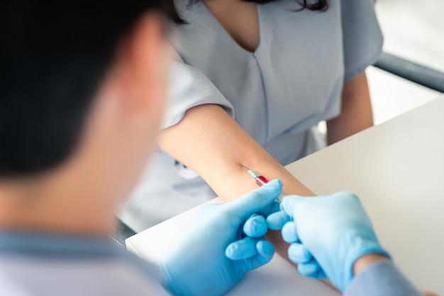 Médico, usando, siringa, leva, sangue, de, paciente, braço