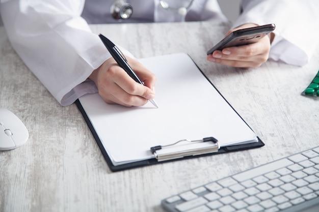 Médico usando smartphone e escrevendo em uma prancheta na clínica.
