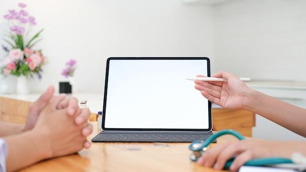 Médico usando tablet discussão algo com o paciente.