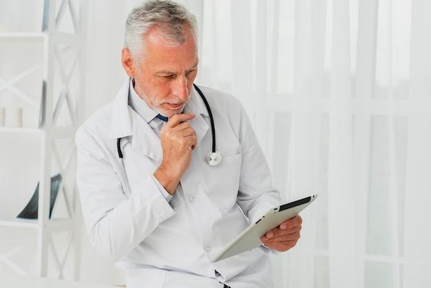 Médico usando tablet enquanto a mão está no queixo