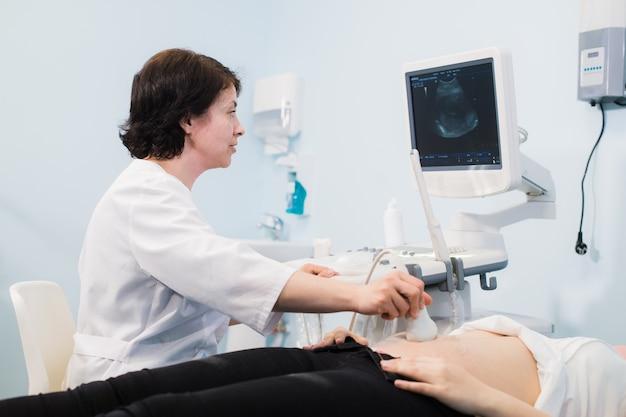 Médico usando ultrassom e triagem de estômago de mulher grávida