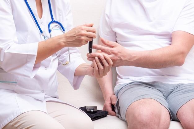 Médico usar detector de glicose no sangue para o paciente